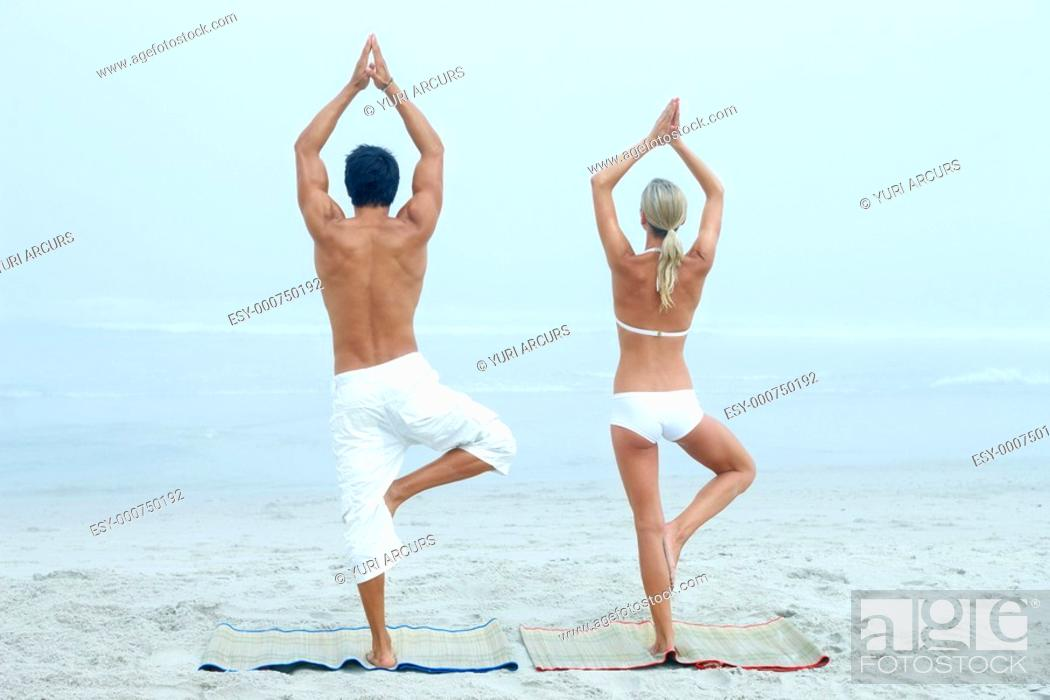 Stock Photo: Rear view of a man and woman practicing yoga at the beach.