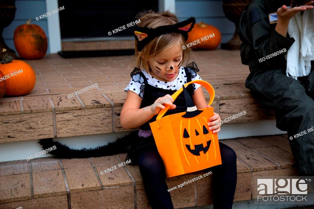 Photo de stock: Girl in cat costume peering into trick or treating bag on porch stairway.