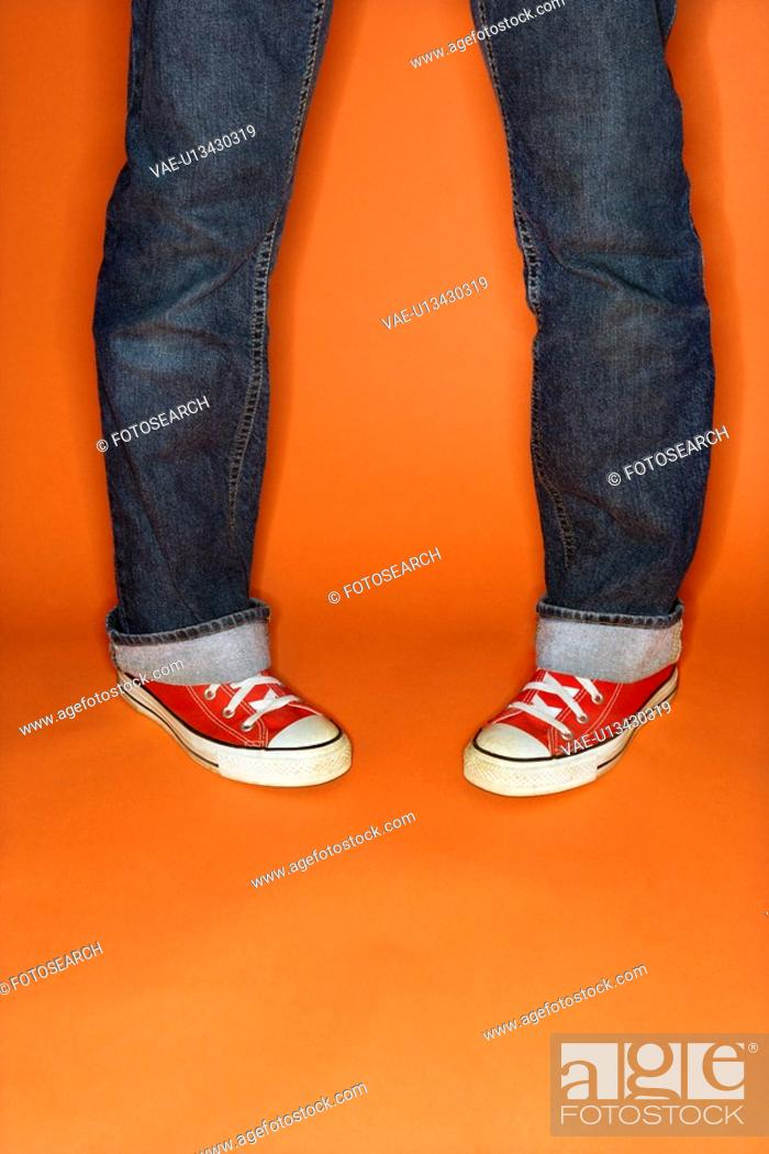 Stock Photo: Person in jeans and sneakers with feet turned inward.