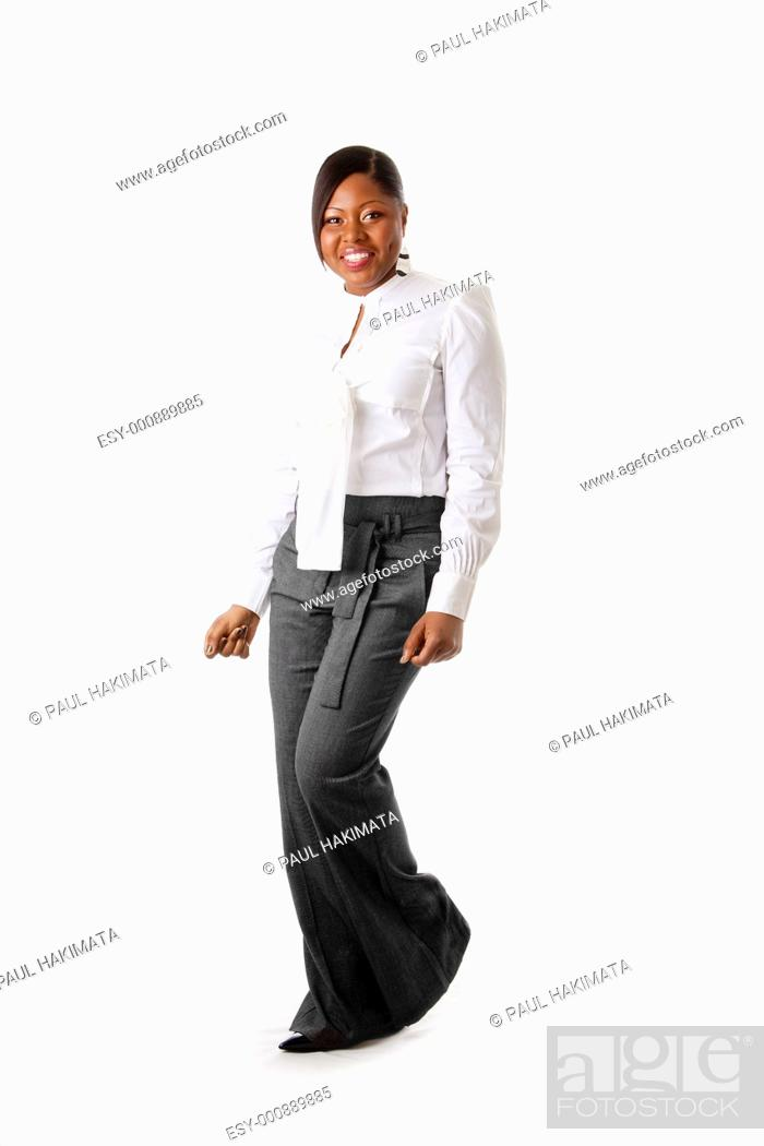 Stock Photo: Beautiful African American business woman with attitude dressed in a white shirt and gray pants standing, dancing happy, isolated.