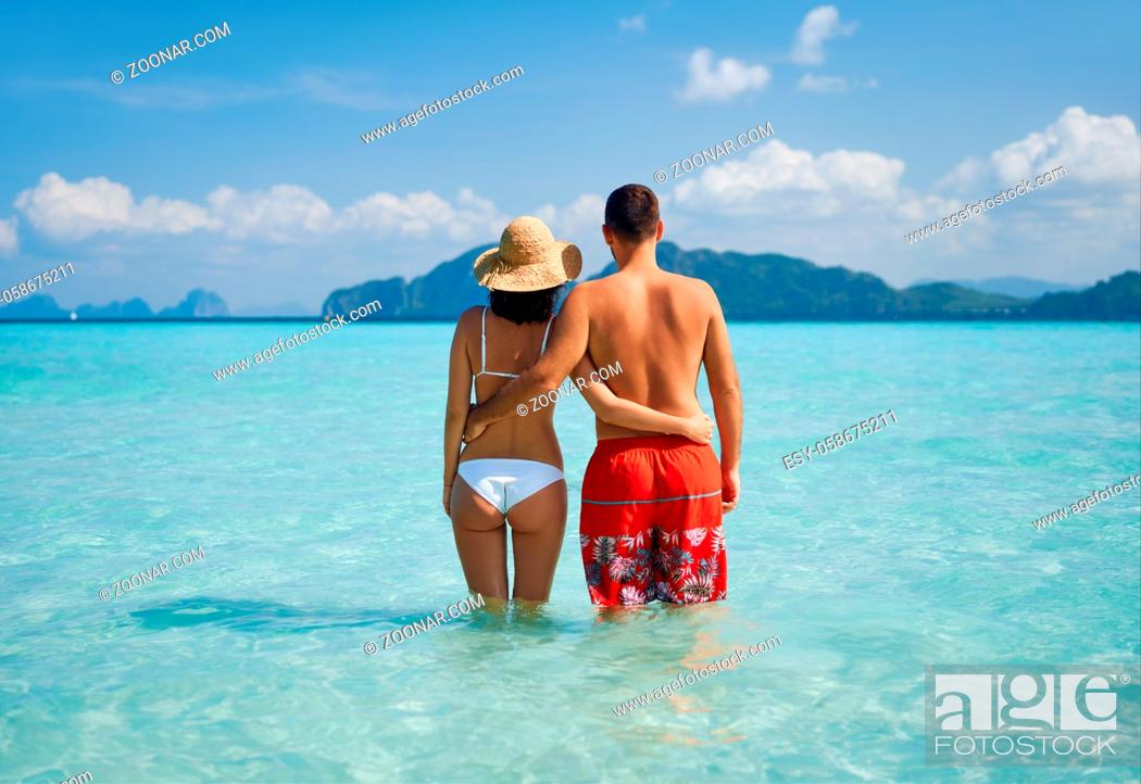 Stock Photo: Romantic couple in love hugging on tropical beach enjoying warm ocean water. Summer vacation concept, travel destination. Rear view.