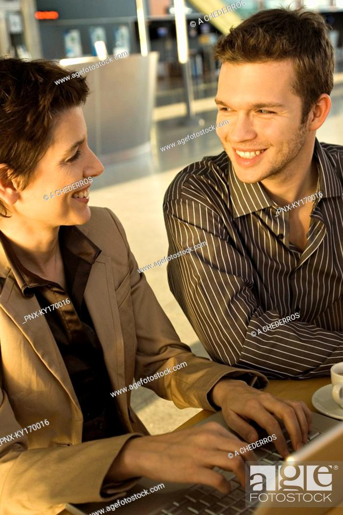 Stock Photo: Businesswoman sitting with a businessman and smiling.