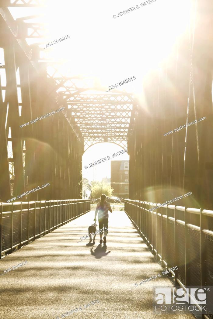 Stock Photo: A woman and her dog on a trail on an old railroad bridge by the Spokane River in Spokane, Washington, USA.