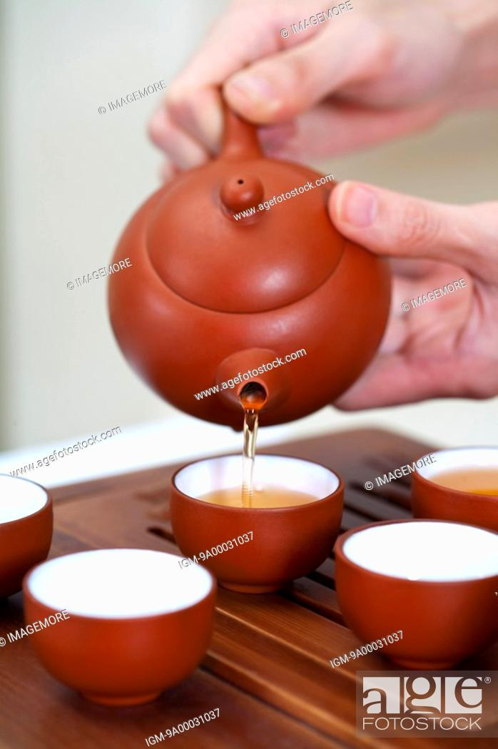 Stock Photo: Tea, Human hands holding a teapot and pouring tea into tea cups.