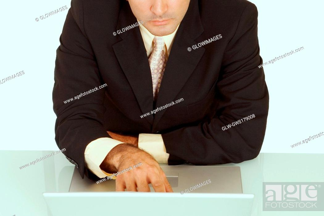 Stock Photo: Mid section view of a businessman using a laptop.