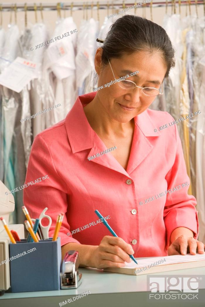 Stock Photo: Asian female dry cleaner writing at counter.