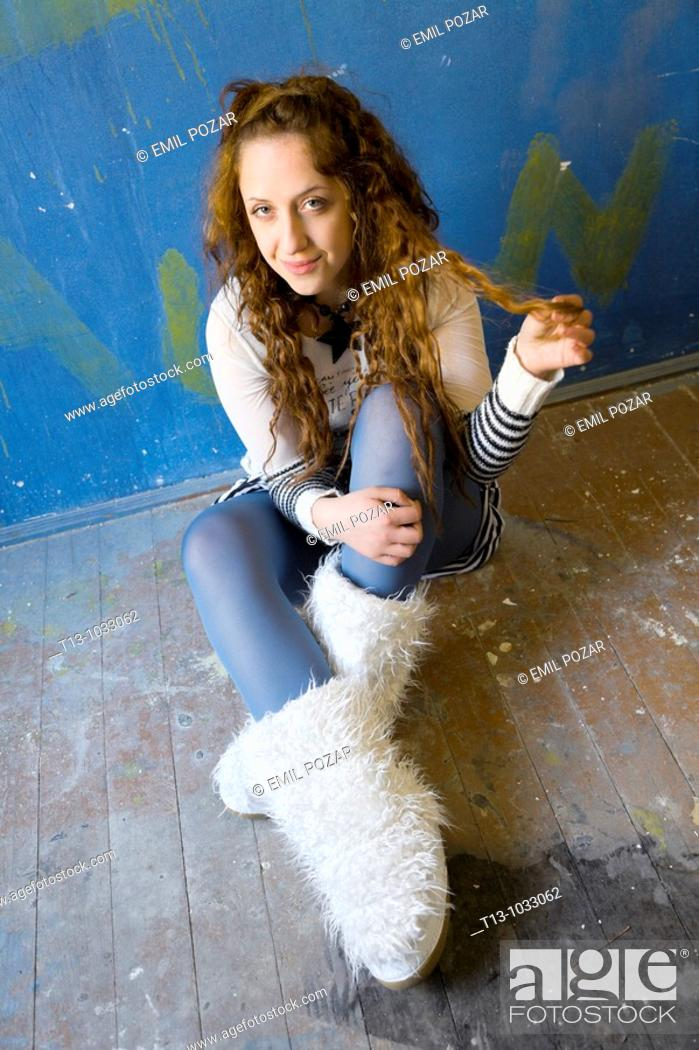 Stock Photo: Young woman is sitting in a room and holding a patch of her long curly hair.