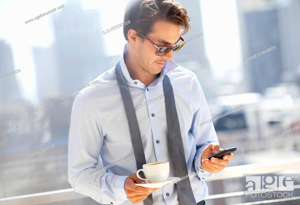 Stock Photo: Businessman with coffee checking cell phone on urban balcony.