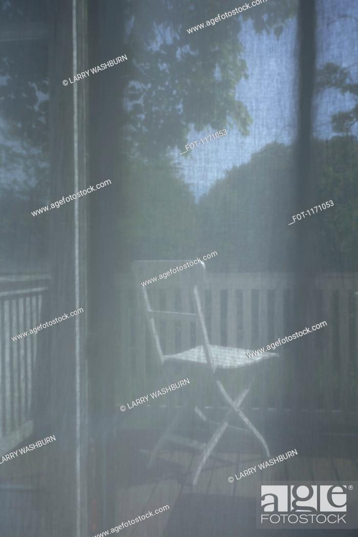 Stock Photo: Looking through a transparent curtain onto a deck.