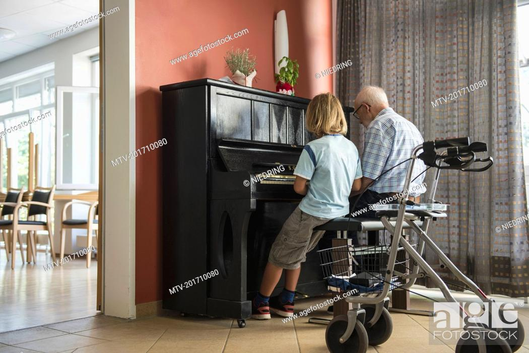 Imagen: Grandfather teaching piano instrument to his grandson.