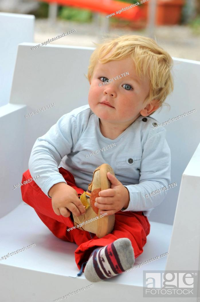 Stock Photo: Toddler, taking off shoes.