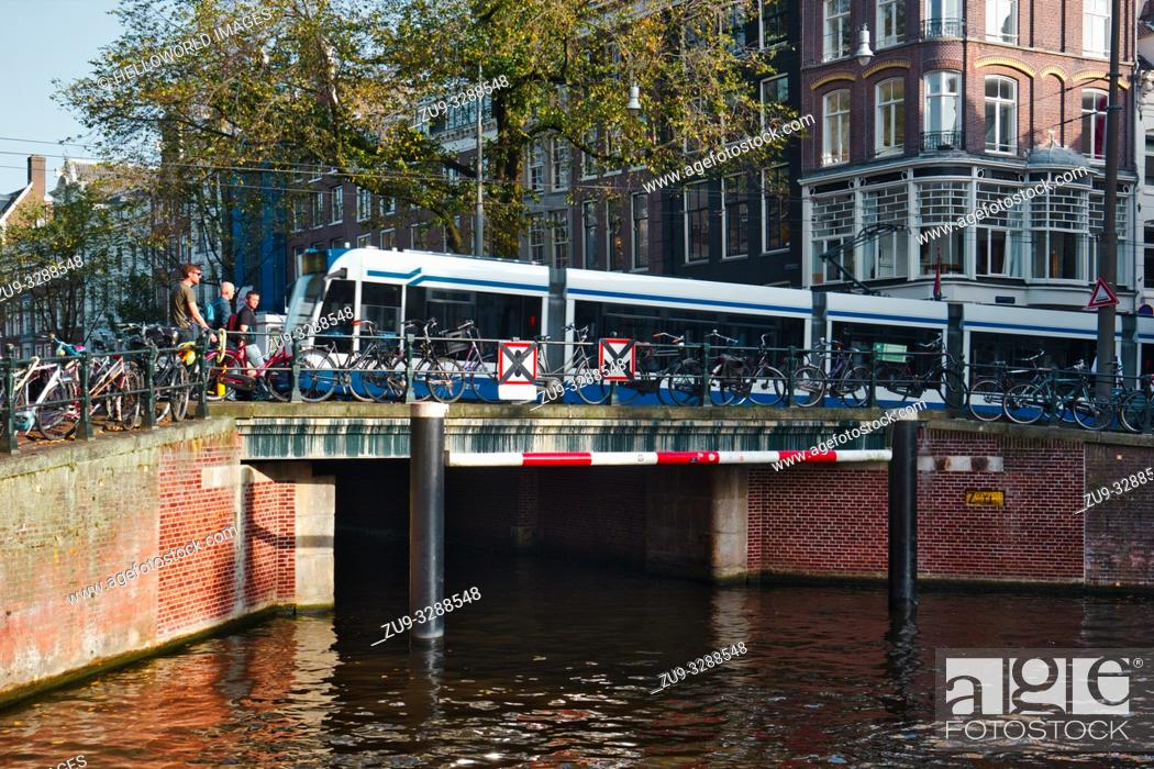 Photo de stock: Tram crossing bridge over canal and parked bikes, Amsterdam, Netherlands, Europe.