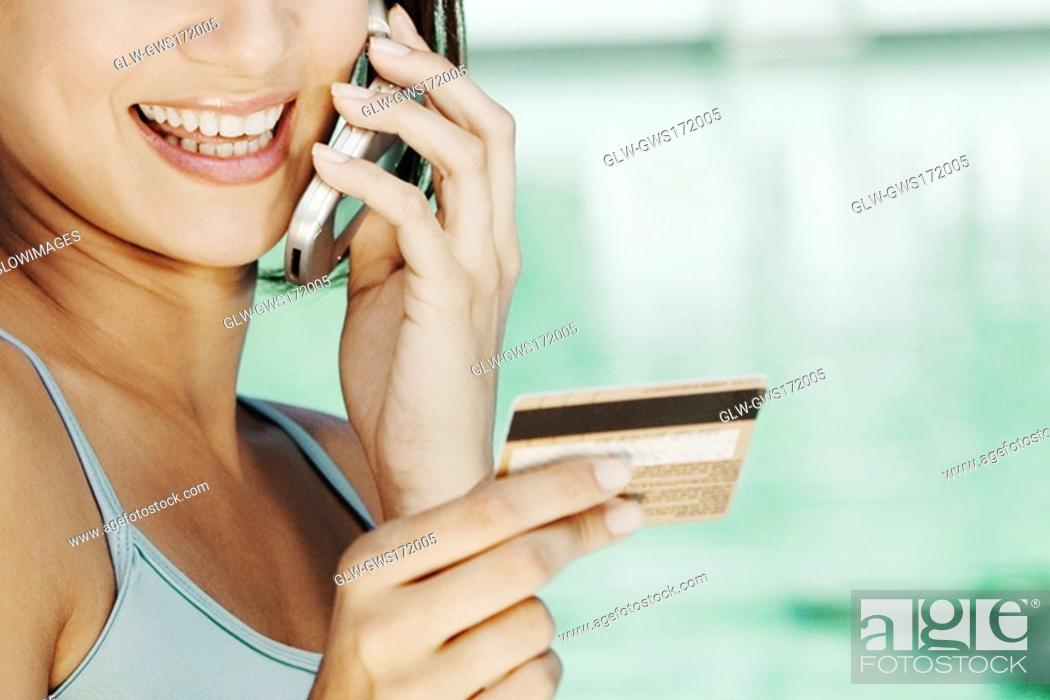 Stock Photo: Close-up of a young woman holding a credit card and talking on a mobile phone.