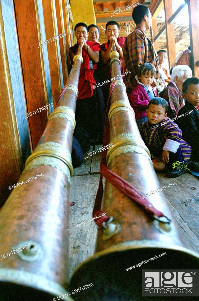 Stock Photo: At the Wangdi Tsechu in Bhutan traditional horns are blown by young boys.