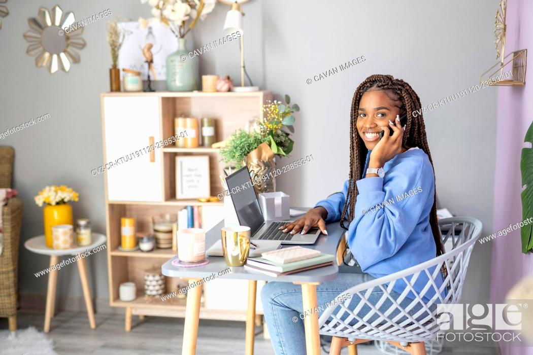Stock Photo: Businesswoman working and talking on her mobile phone at home.