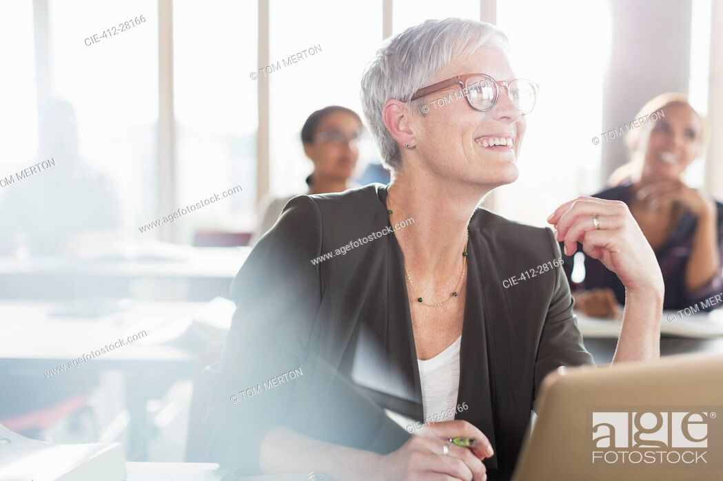 Stock Photo: Smiling senior woman at laptop in adult education classroom.