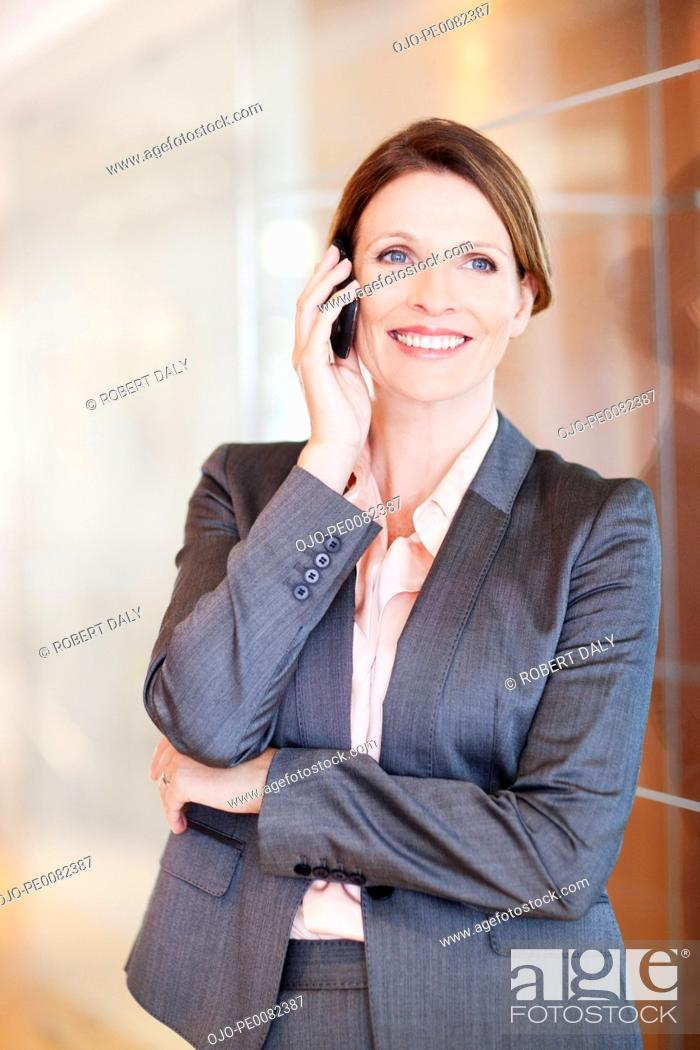 Stock Photo: Smiling businesswoman talking on cell phone.