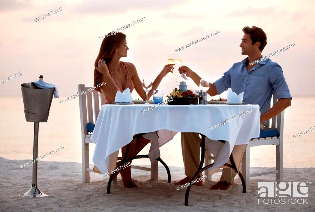 Stock Photo: Portrait of an attractive young couple toasting champagne and enjoying dinner in beach.