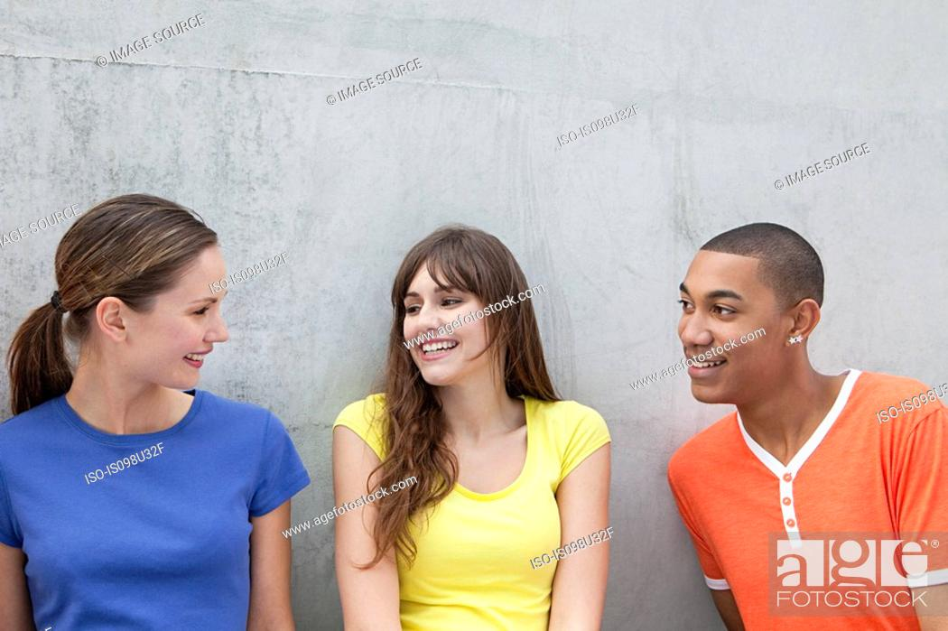 Stock Photo: Young man and two young women.