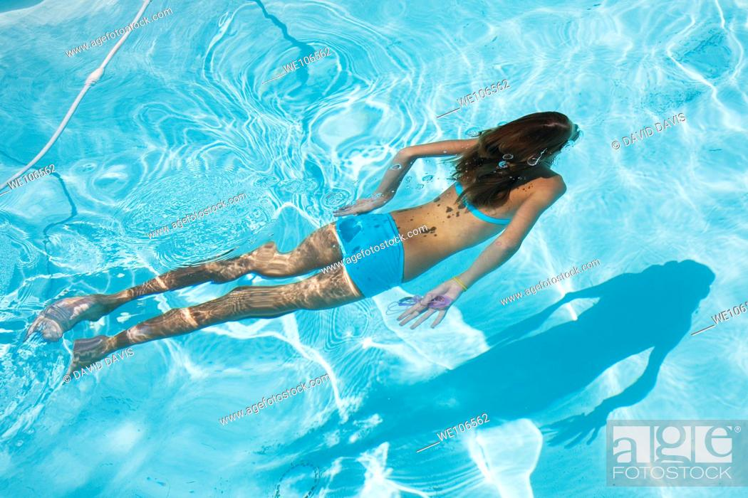 Stock Photo: Young girl swimming under water.