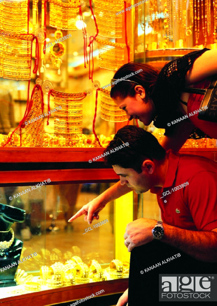 Stock Photo: Tourists looking at jewellery in the Gold Souq in Dubai, United Arab Emirates.