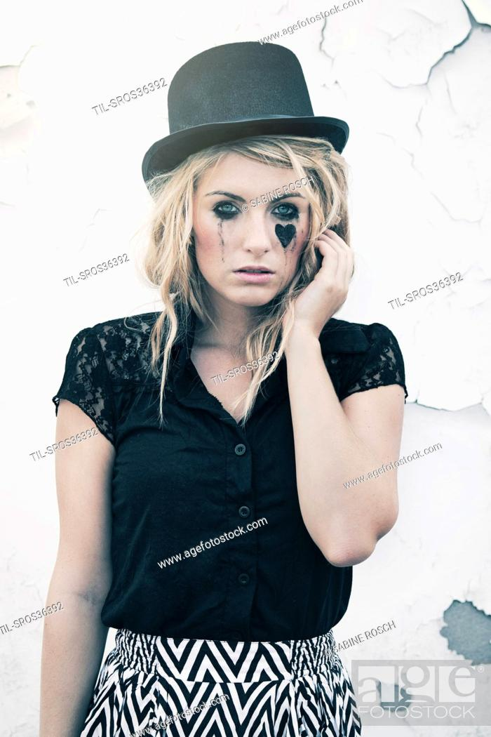 Imagen: close up of a young woman with blonde hair wearing a top-hat.