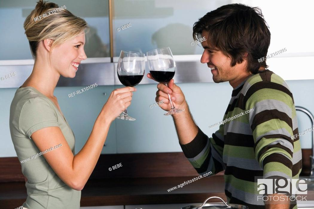 Stock Photo: Young couple in modern kitchen toasting at each other with red wine.