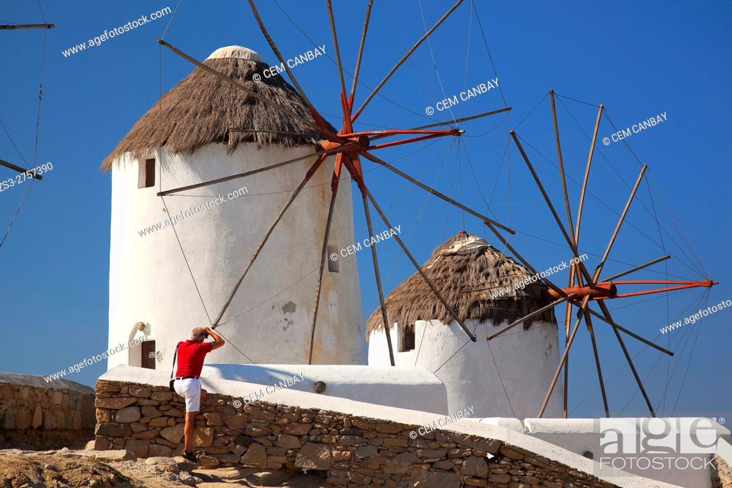 Stock Photo: Tourist taking the photos of the traditional windmills, Mykonos, Cyclades Islands, Greek Islands, Greece, Europe.