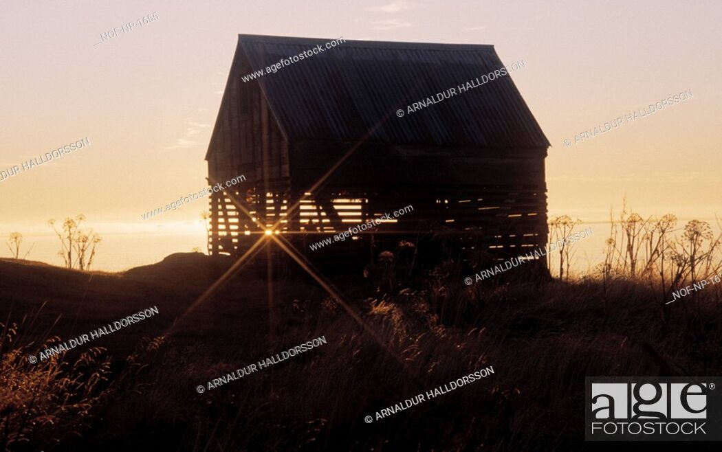 Stock Photo: Sunset behind the silhouette of a barn.
