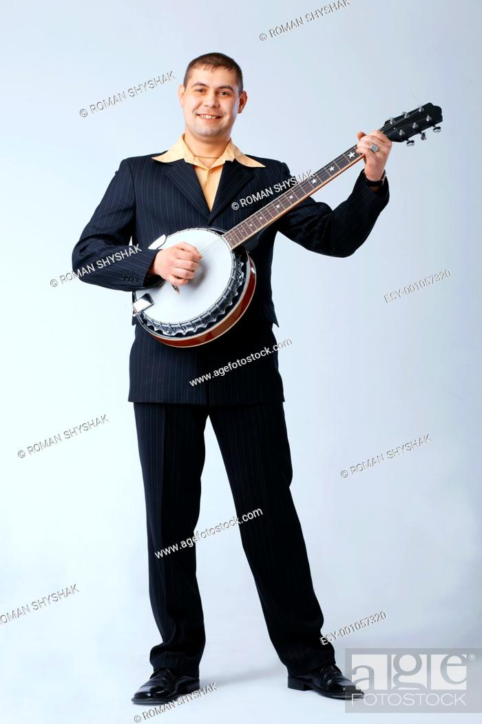 Stock Photo: Man in suite is standing and playing on banjo against white, full length.