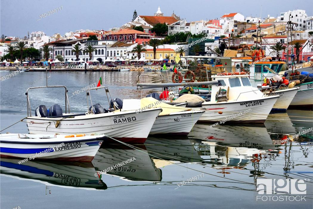 Stock Photo: Traditional fishing boats moored in the harbour, in background old town with historic food market, Ciencia Viva - cultural center and Sao Sebastiao church.