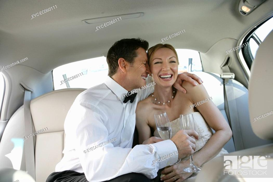 Stock Photo: Mature couple laughing in the backseat of a car.