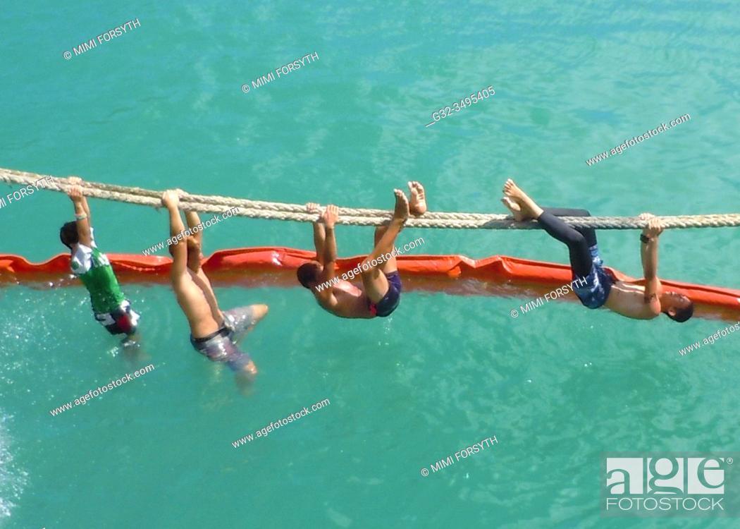 Stock Photo: boys play on ship's rope, Hakahau harbor, Ua Pou, Marquesas, French Polynesia.