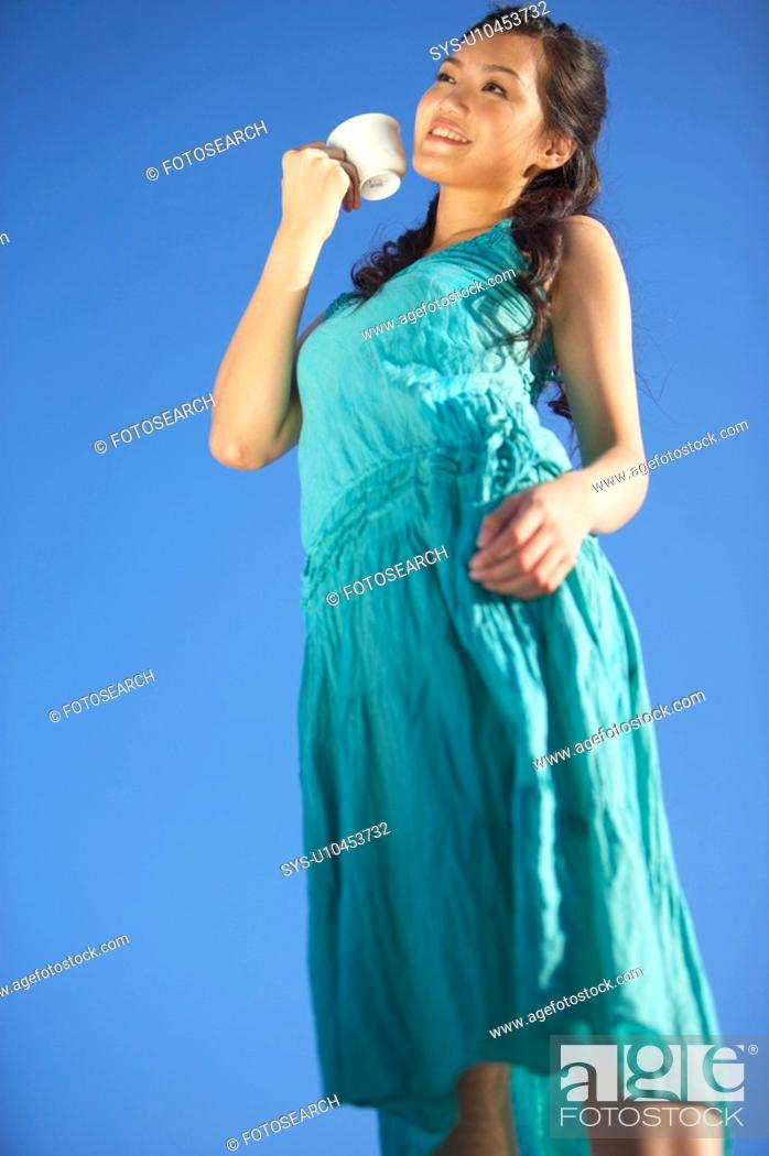 Stock Photo: Young Lady Drinking Cup of Tea, Standing, Smiling.