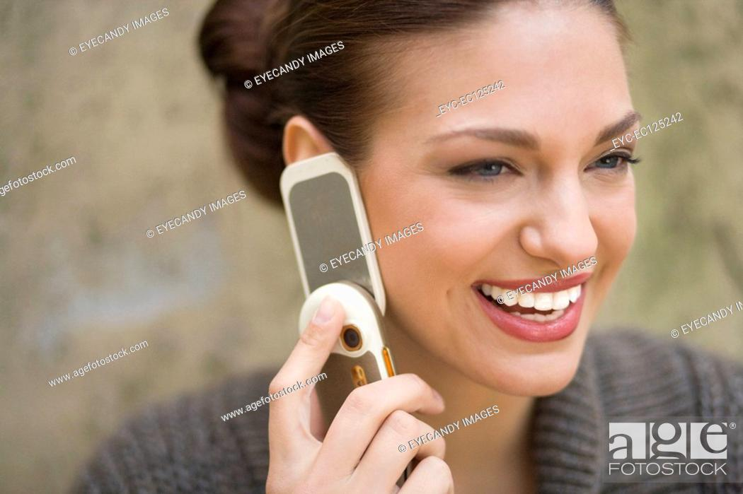 Stock Photo: Close-up of young happy woman using mobile phone in yard.