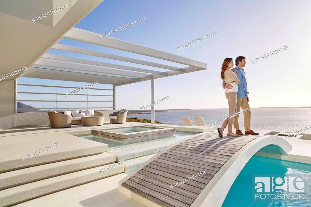 Stock Photo: Couple standing on bridge above a swimming pool enjoying the view.