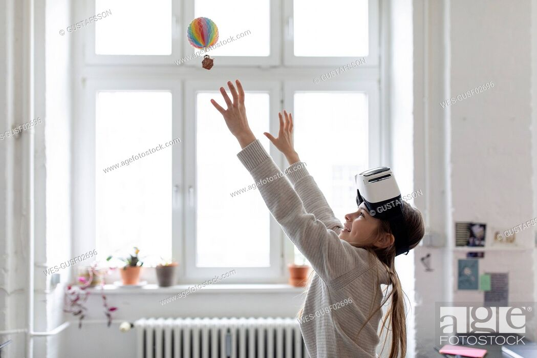 Stock Photo: Girl with VR glasses trying to catch hot-air balloon in office.