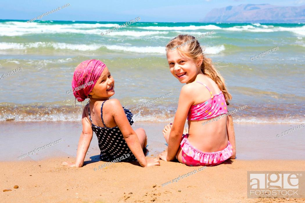 Stock Photo: Two girls sitting on beach looking back, portrait, Castellammare del Golfo, Sicily, Italy.