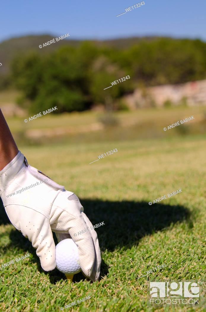 Stock Photo: Golfer with white glove puts golf ball on tee.