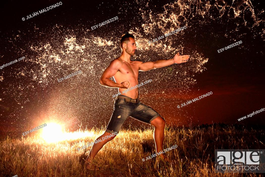 Stock Photo: Specialist in Karate performing exercises with water on stage.