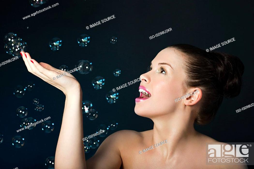 Stock Photo: Young brunette woman with floating bubbles.