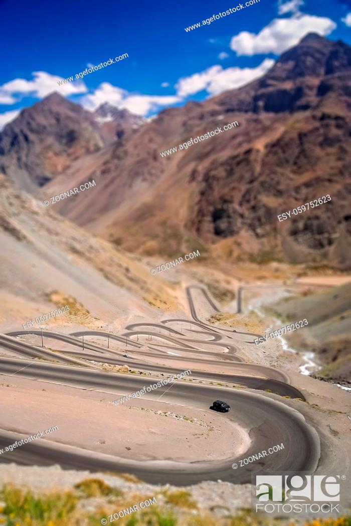 Stock Photo: Car driving uphill on the twisting and turning switchback road through high Andes in Chile, South America.