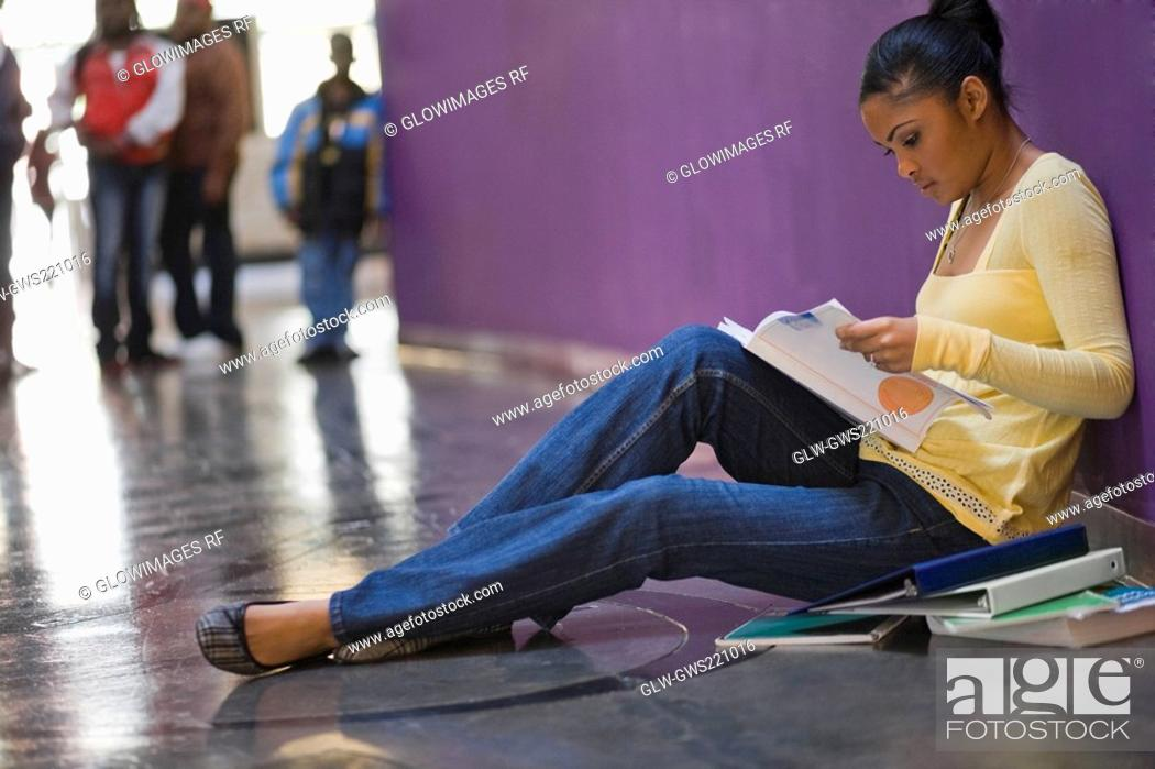 Stock Photo: Side profile of a young woman reading a textbook in a corridor.