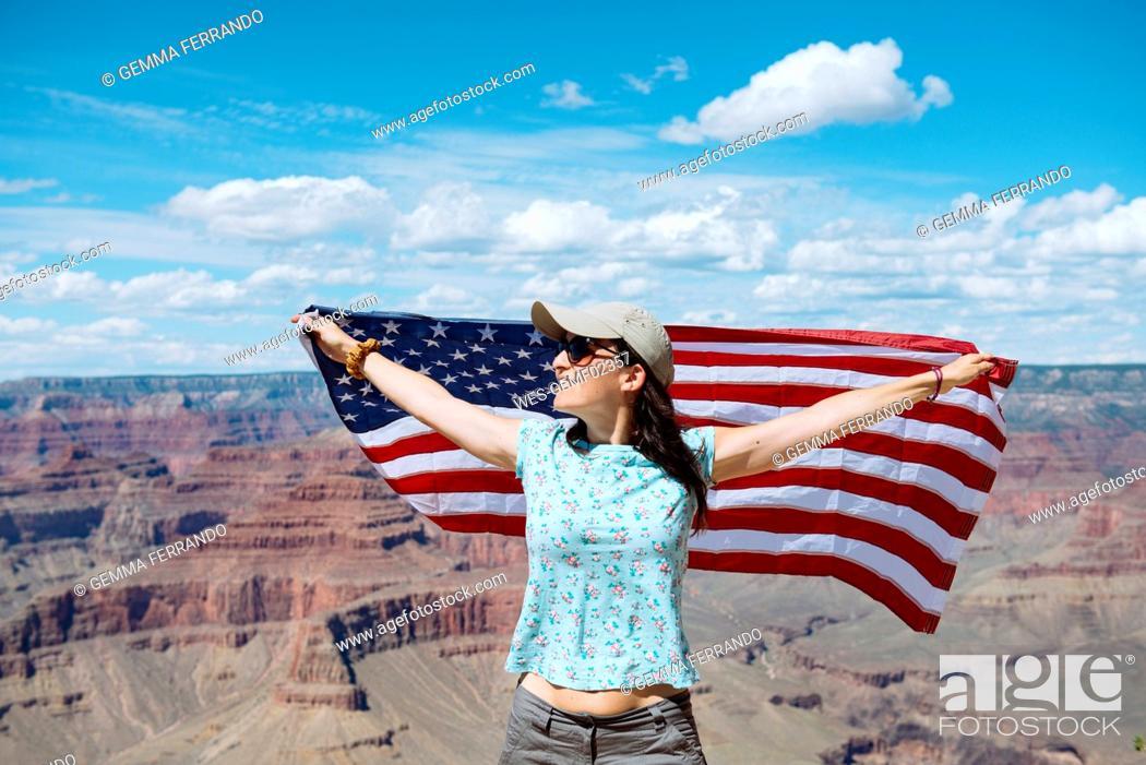 Stock Photo: USA, Arizona, smiling woman with American flag at Grand Canyon National Park.