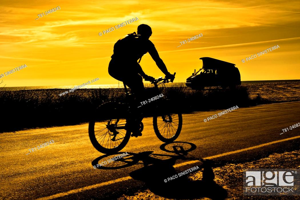 Stock Photo: cyclist and motor home at dawn in Alcocebre, Spain.