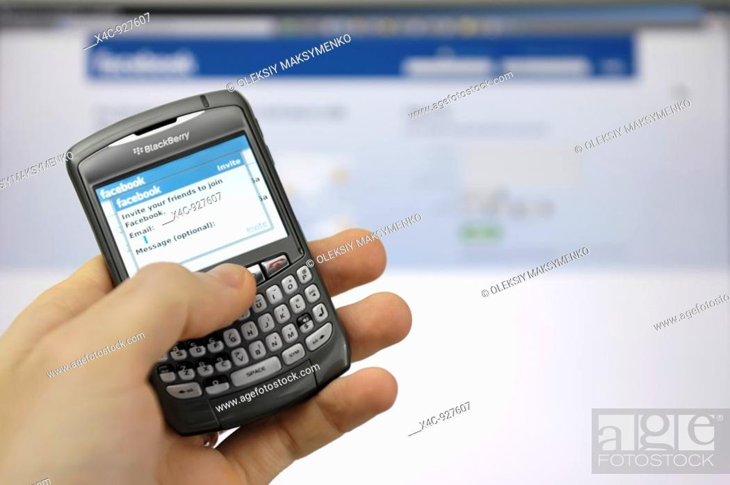 Stock Photo: Facebook invitation screen on a display of Blackberry smartphone.