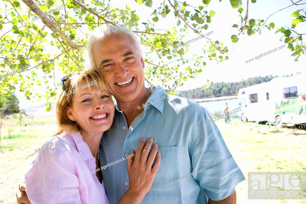 Stock Photo: Mature couple arm in arm by motor home outdoors, smiling, portrait.