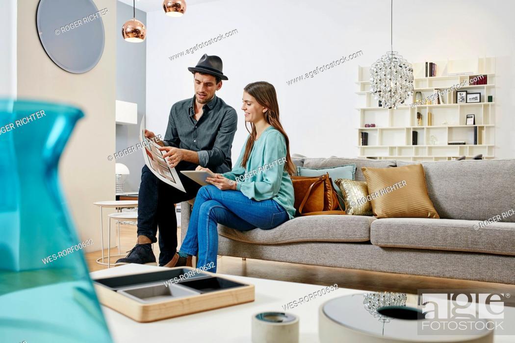Stock Photo: Couple choosing furniture in shop, using digital tablet.