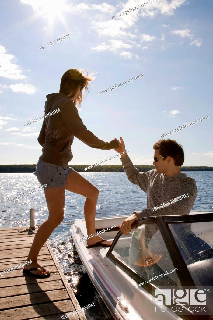 Stock Photo: Couple climbing into speedboat.