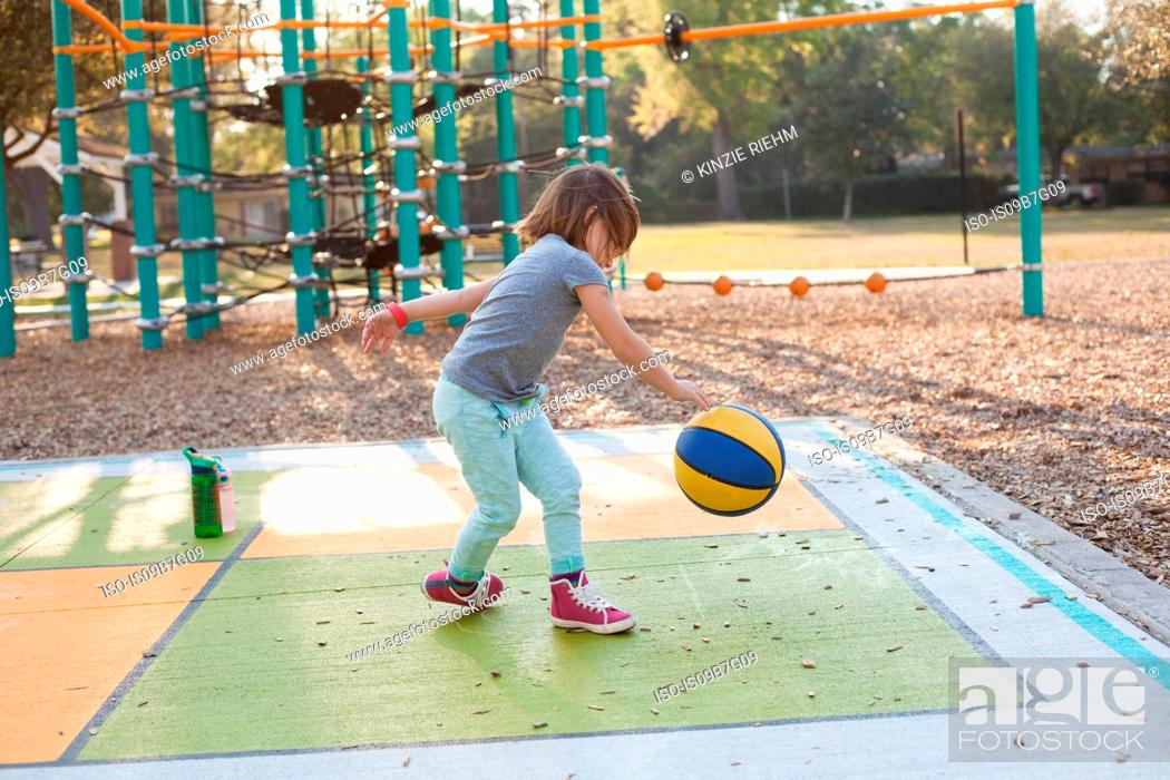 Stock Photo: Girl bouncing basketball in playground.